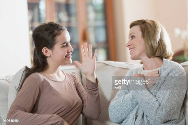 teenage girl with mother, using sign language - signing stock pictures, royalty-free photos & images
