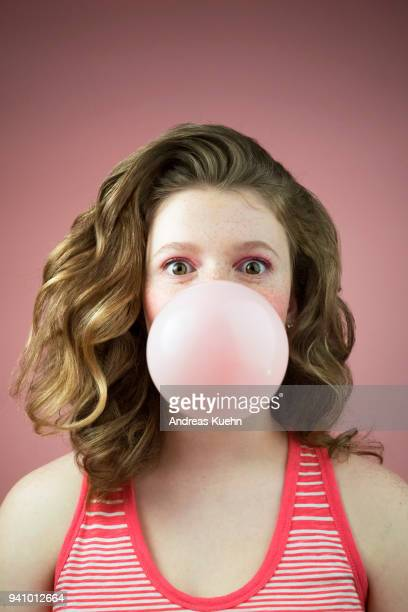Teenage girl with pale skin, freckles and wavy long hair looking into the camera with big eyes while blowing a big bubble with her pink bubblegum, portrait.