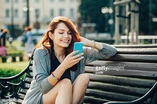 Teenage girl with phone on a bench