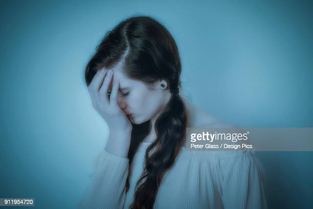 teenage girl with pigtails looking down with hand covering her face - down blouse stock-fotos und bilder