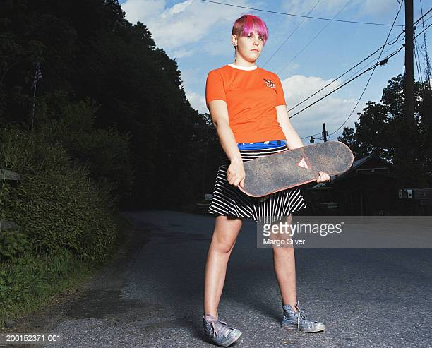 teenage girl (14-16) with pink hair holding skateboard, portrait - tomboy stock photos and pictures