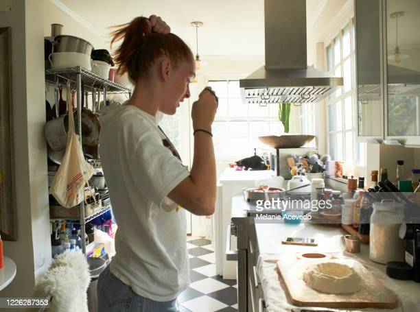 teenage girl with red long straight hair brown eyes and freckles standing up in the kitchen making homemade pasta with flour and raw egg cracked in the middle on a cutting board hair putting up in a pony tail wearing a t shirt looking down at the counter - nostalgia stock pictures, royalty-free photos & images