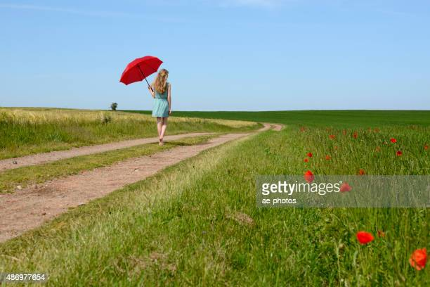 Teenage girl with red parasol walking along dirt road