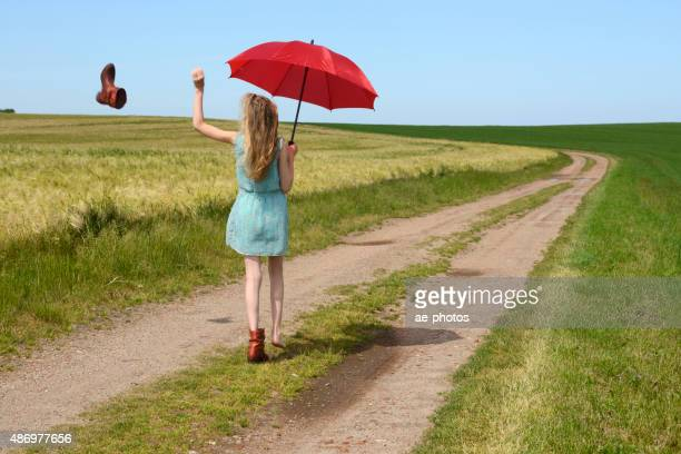 teenage girl with red parasol walking along dirt road - girl strips stock pictures, royalty-free photos & images