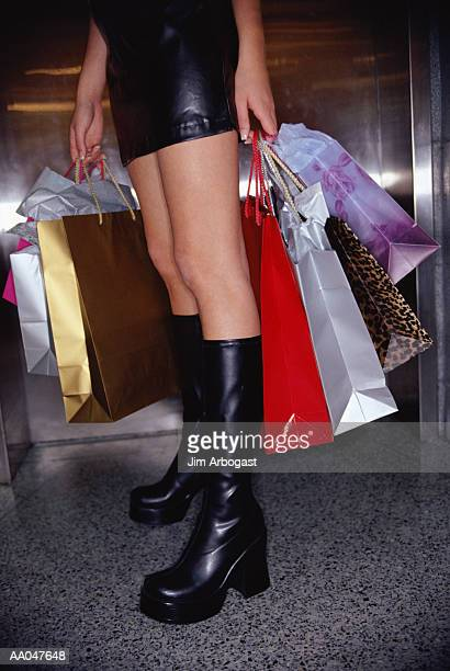 Teenage girl (16-18) with shopping bags, low section