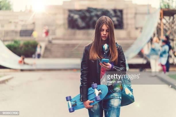 Adolescente con patín en el texto de la ciudad