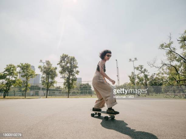 teenage girl with skateboard in the park on a sunny day. - skating stock pictures, royalty-free photos & images
