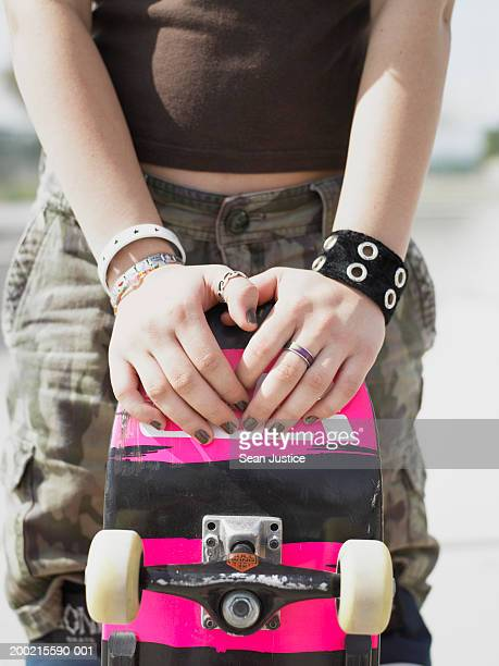 teenage girl (14-16) with skateboard, mid section - combat sport foto e immagini stock