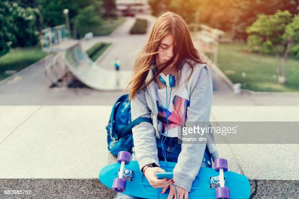 teenage girl with skateboard texting on smartphone - school girl shoes stock pictures, royalty-free photos & images