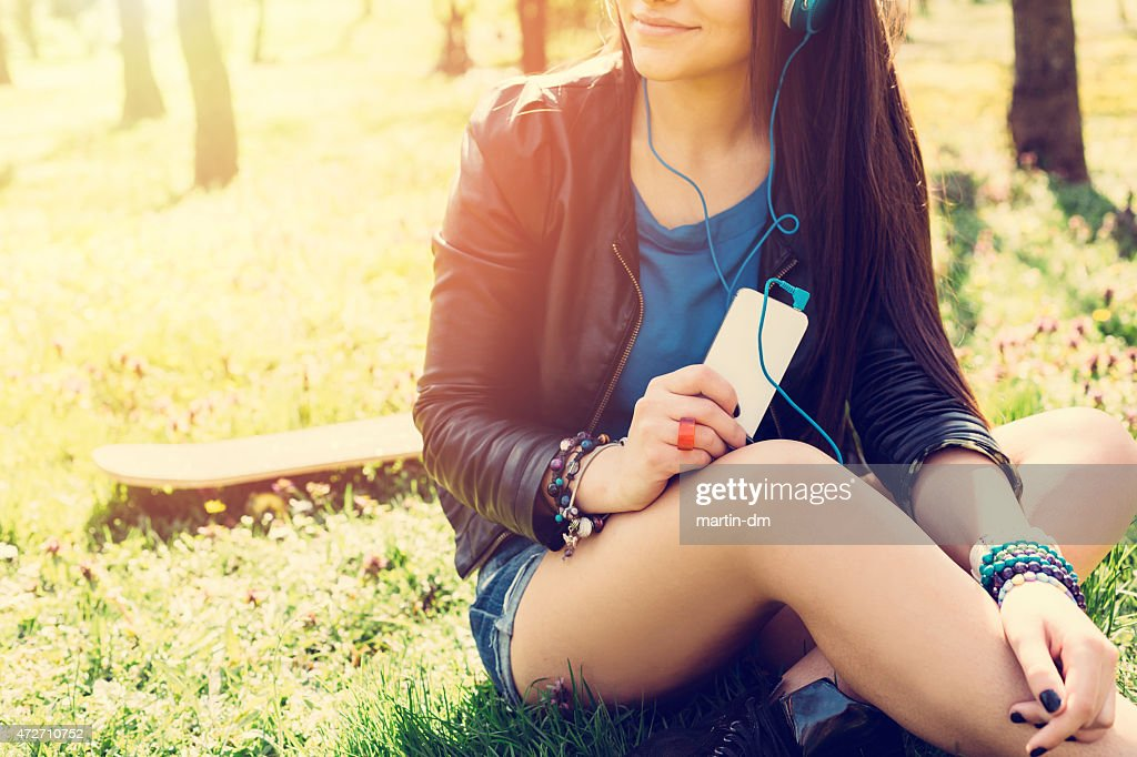 Teenage girl with smartphone sitting in the grass : Stock Photo