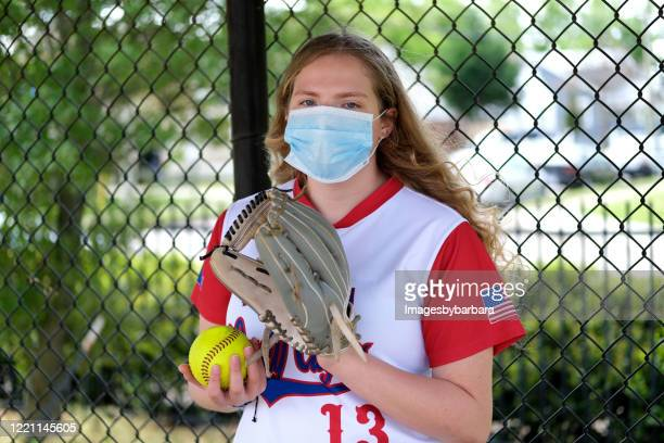 teenage girl with softball uniform and healthcare masks - softball sport stock pictures, royalty-free photos & images