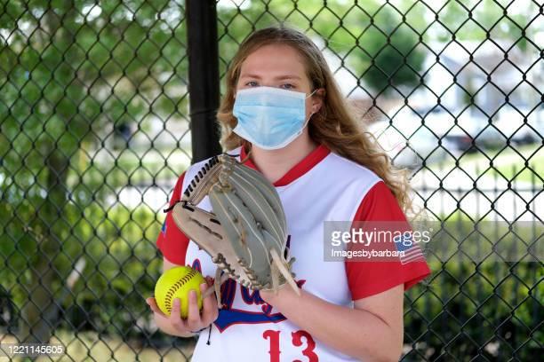 ソフトボールのユニフォームとヘルスケアマスクを持つ10代の少女 - sports uniform ストックフォトと画像