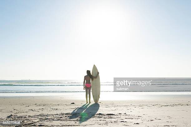 teenage girl with surfboard on the beach - alleen één tienermeisje stockfoto's en -beelden