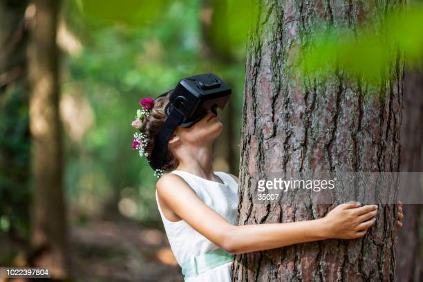 teenage girl with virtual reality glasses hugging a tree in the forest