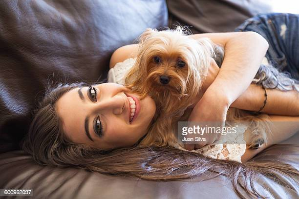 Teenage girl with Yorkshire Terrier dog on sofa