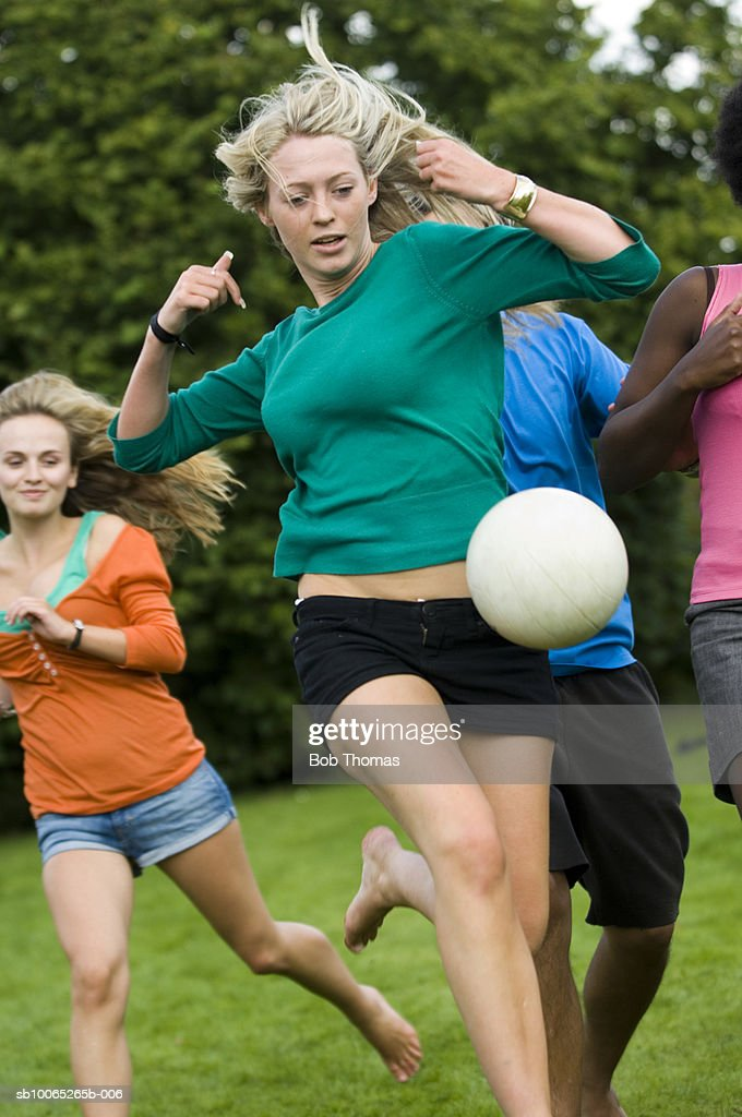 Teenage girl (16-17) with young woman playing soccer ball : Foto stock