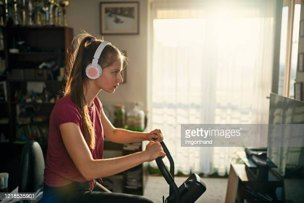 teenage girl working out on exercise bike at home - effort stock pictures, royalty-free photos & images