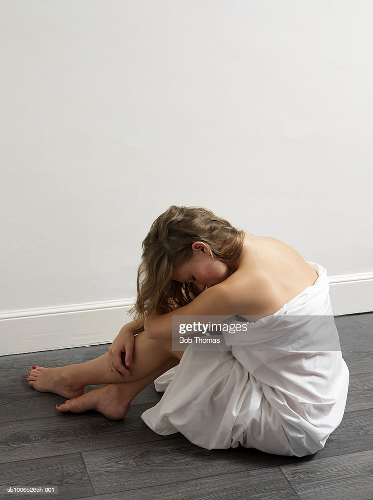 Teenage girl (16-17) wrapped in blanket resting head on knees, side view : Foto stock