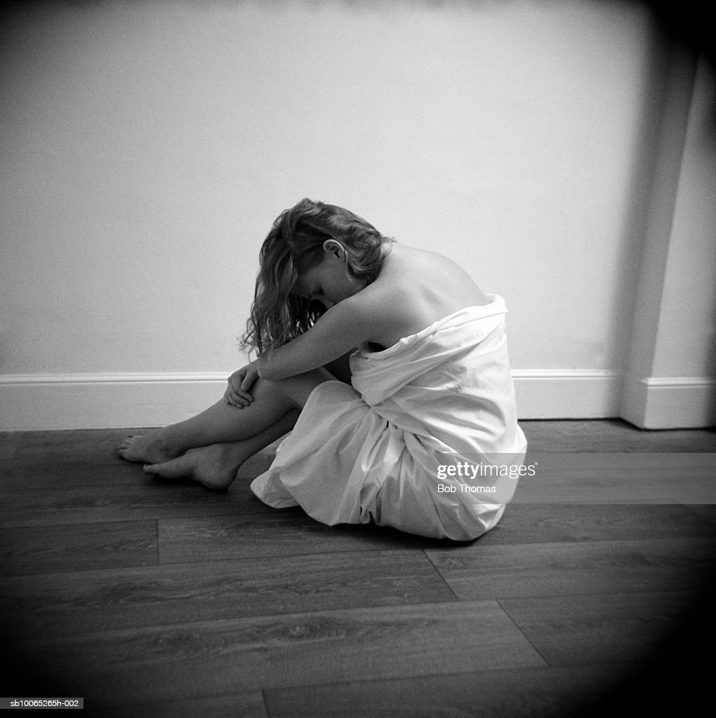 Teenage girl (16-17) wrapped in blanket resting head on knees, side view (B&W) : Foto stock