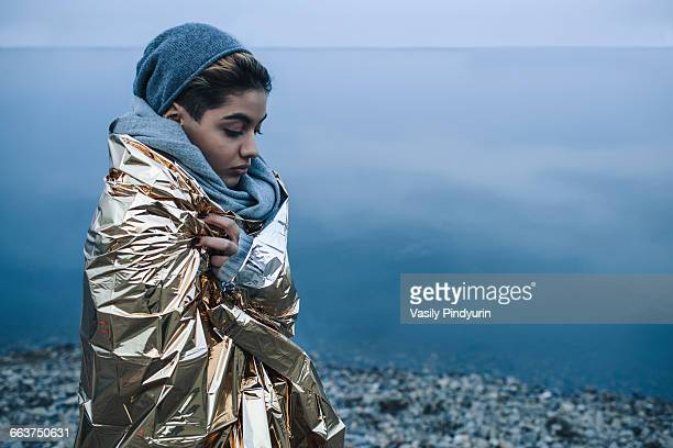 teenage girl wrapped in golden plastic at lakeshore during winter - extreme weather stock photos and pictures