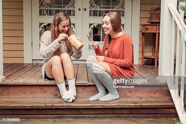 teenage girlfriends eating peanut butter by the spoon on porch. - girls in socks stock photos and pictures