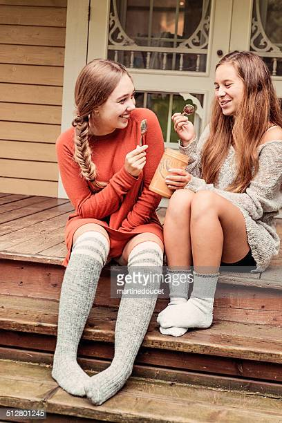 Teenage girlfriends eating peanut butter by the spoon on porch.