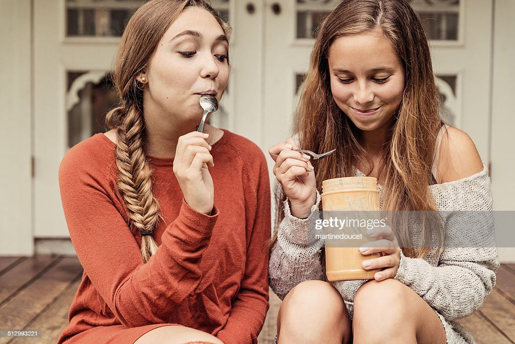 Teenage girlfriends eating peanut butter by the spoon on porch. : Stock Photo