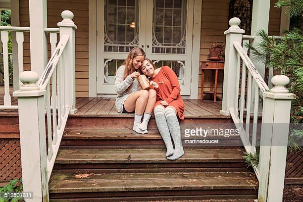 Teenage girlfriends eating peanut butter on house porch rainy day.