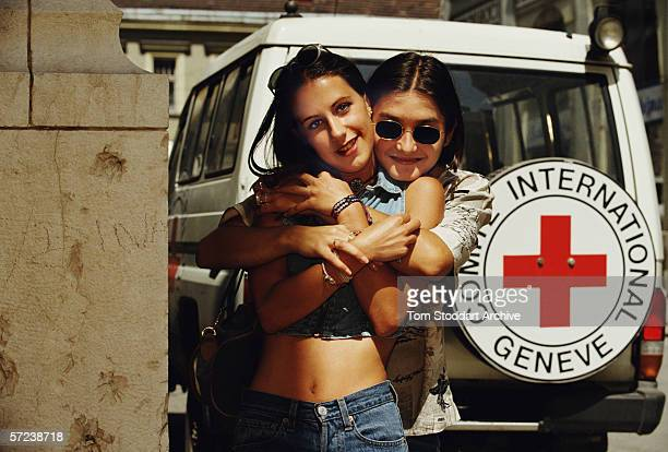 Teenage girlfriends embrace near a Red Cross vehicle in Sarajevo as the city begins to come to life again after four years of siege and conflict