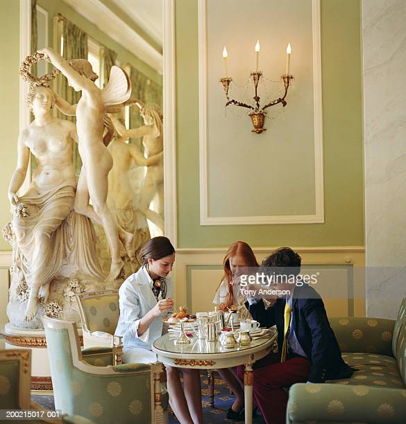 teenage girls and boy (13-15) at table in lobby - high society stock pictures, royalty-free photos & images