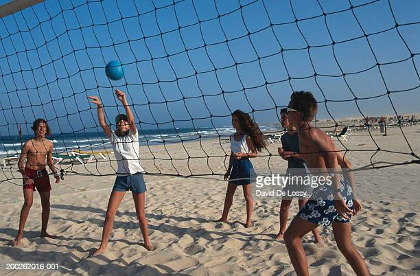 teenage girls and boys (16-17) playing beach volley ball - beach volley photos et images de collection