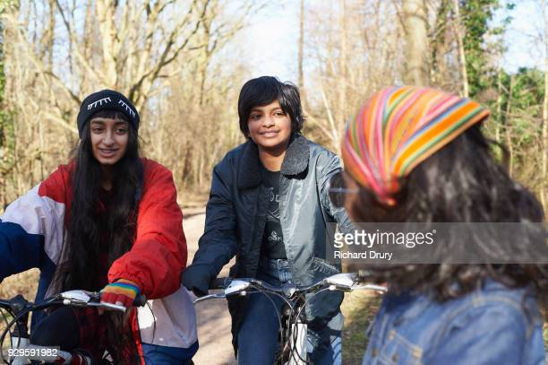 Teenage girls and young boy talking on cycle track