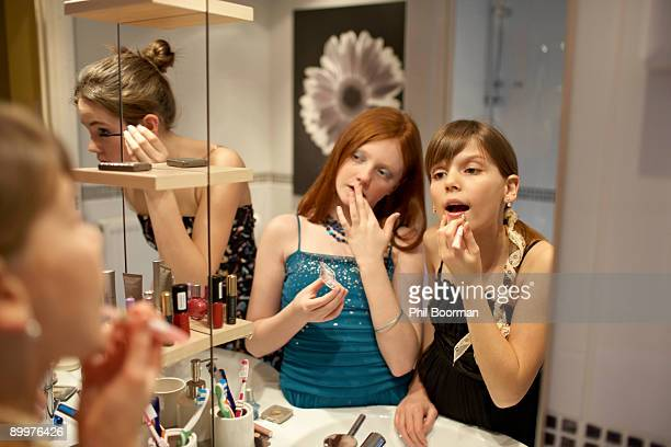 teenage girls applying make-up - girl in mirror stock-fotos und bilder