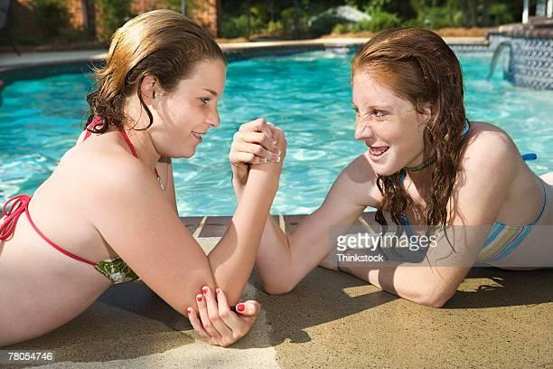Teenage girls arm wrestling next to pool