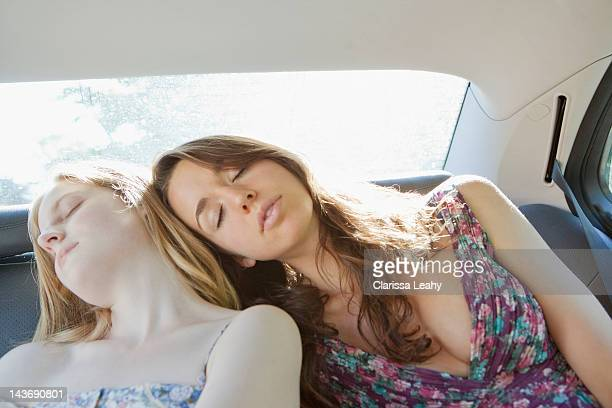 Teenage girls asleep in back seat of car