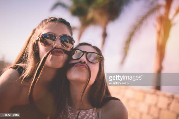 teenage girls being silly making funny faces with hair mustaches - mustache stock pictures, royalty-free photos & images