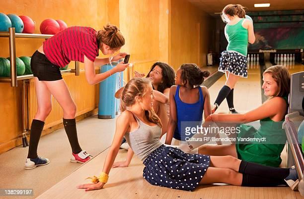 Teenage girls bowling together