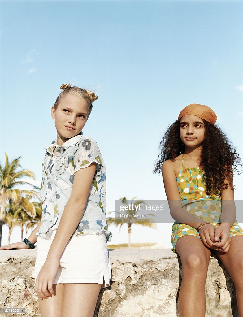 Teenage Girls by a Stone Wall Wearing Summer Clothing : Stock Photo