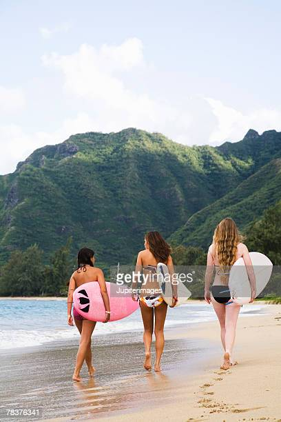 Teenage girls carrying surfboards