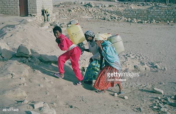 Teenage girls carrying water home from a well in central Eritrea 2004