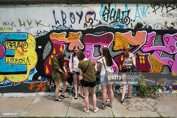 Teenage girls chat alongside the former Berlin Wall at 'East Side Gallery' in Berlin At Midnight on November 9th East Germany's Communist rulers...