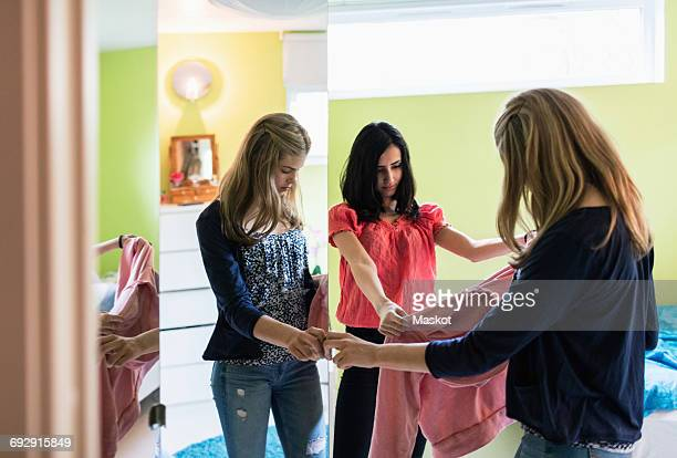 Teenage girls choosing clothes by closet at home