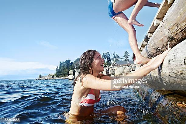 Teenage girls climbing pier