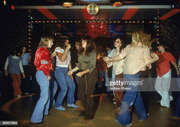 Teenage girls dance in their socks under a nightclub disco ball 1970s