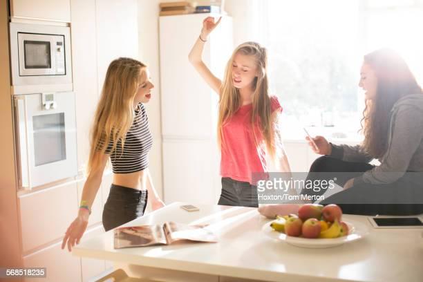 Teenage girls dancing in sunny kitchen