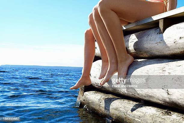 Teenage girls dangling legs over pier