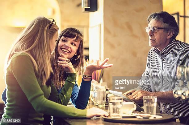 Teenage girls debating in a coffee bar