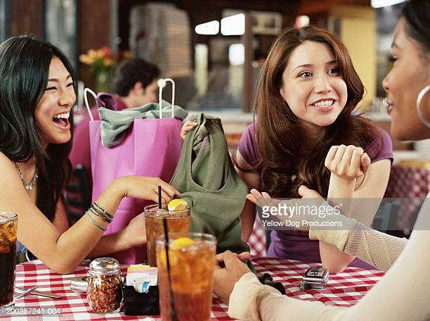 Teenage girls (11-22) discussing clothing shopping at restaurant table