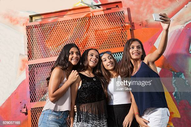 Teenage girls doing a selfie with phone outdoors