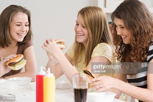 Teenage girls eating hamburgers